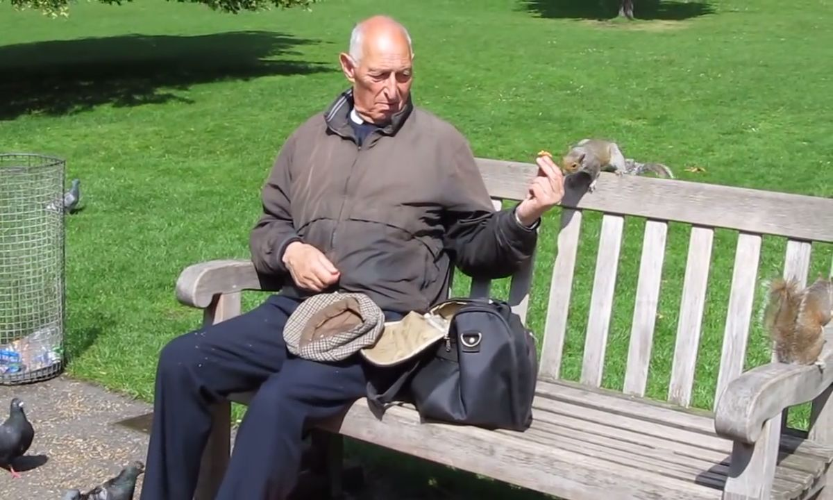 man feeding squirrels